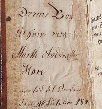 Eiersignatur/inskripsjon skrevet på innsiden av forpermen (Denne Bog tilhører mig Marthe Aadsdatter Hove)
